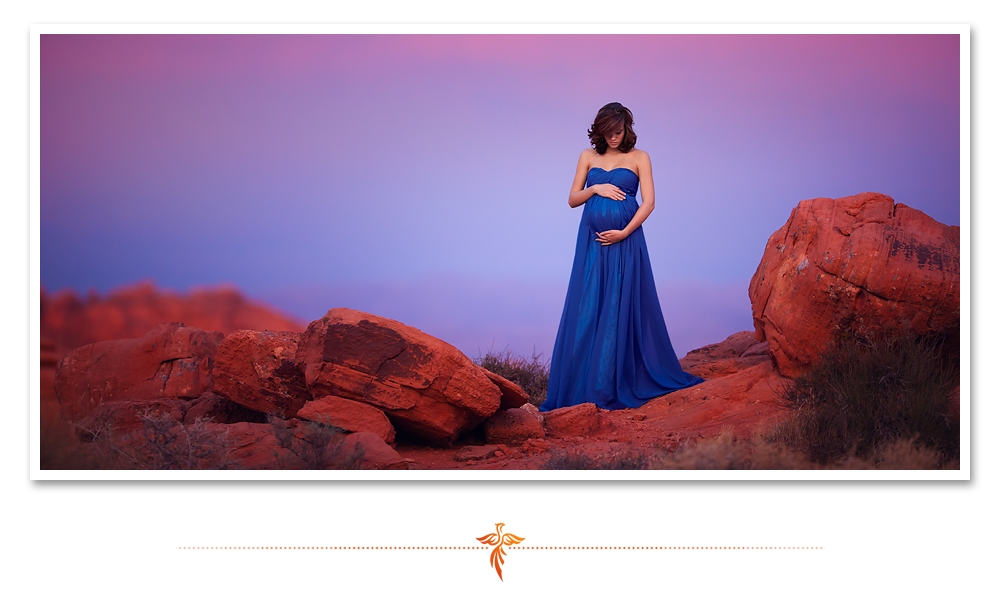 Gorgeous expecting mother in a royal blue gown poses in the red rocks in front of a purple sunset for her maternity pictures. LJHolloway Photography is a Las Vegas Maternity Photographer.